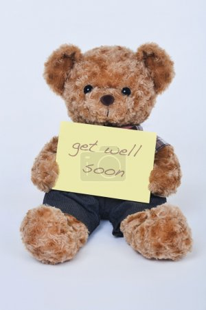 A cute teddy bear holding a yellow sign saying Get Well Soon isolated on a white background