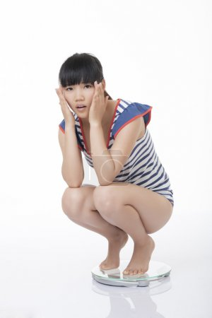 Beautiful Chinese woman weighing herself on a scale and not happy with the results isolated on a white background