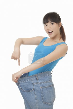 Beautiful Chinese woman wearing fat jeans to illustrate weight loss isolated on a white background