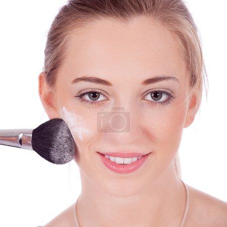 beautiful woman applying make up on face