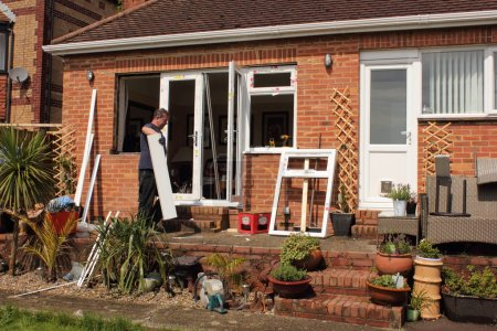 Photo for A window fitter installing new plastic windows and French doors to a bungalow - Royalty Free Image