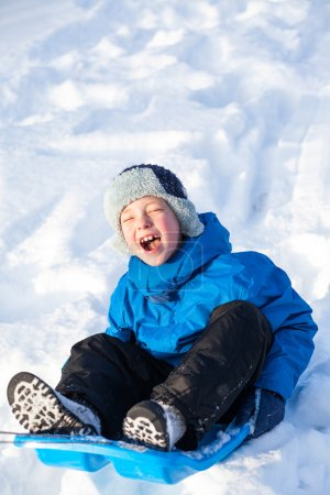 young boy with sled