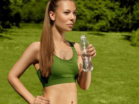 Photo pour Belle femme boit de l'eau après un exercice de remise en forme - image libre de droit