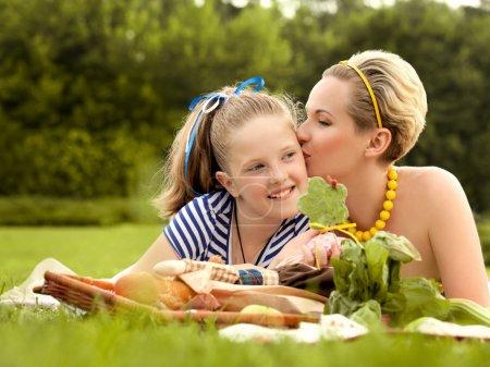 Foto de Feliz madre e hija besos al aire libre. picnic familiar - Imagen libre de derechos