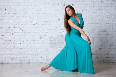 Pretty woman dancer wearing beautiful turquoise dr...