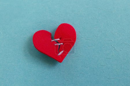 Photo for Small red heart, broken with threaded stitches - Royalty Free Image