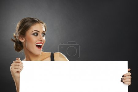 Excited woman holding blank board