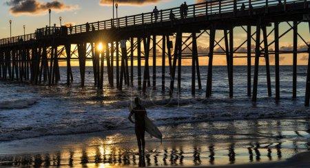 Surfer watching an Oceanside California sunset.