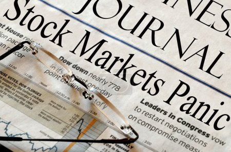 Photo for Stock Market Panics - headlines from a newspaper (fictitious). Reading glasses in foreground. - Royalty Free Image