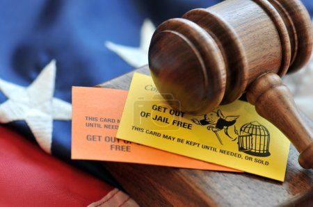 Ellow and orange playing card with gavel atop US flag