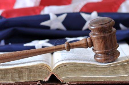 Photo pour Branche judiciaire - marteau sur livre altéré avec drapeau en arrière-plan . - image libre de droit