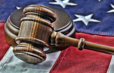 Wooden judge's gavel and American flag