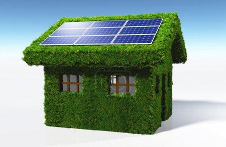 Foto de Una pequeña casa cubierta de hierba en las paredes y el techo, tiene algunos paneles solares colocados en un lado de la cubierta con el sol que se refleja en ellos, sobre un fondo blanco y un cielo azul - Imagen libre de derechos