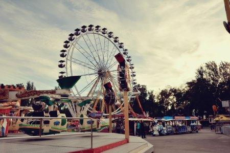 Photo pour Dans le parc d'attractions sur un fond de ciel nuageux la roue - image libre de droit