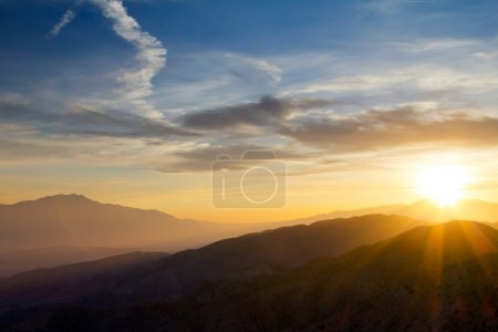 Photo pour Rayons de coucher de soleil colorés sur des montagnes lointaines dans le parc national de Joushua Tree, Californie - image libre de droit