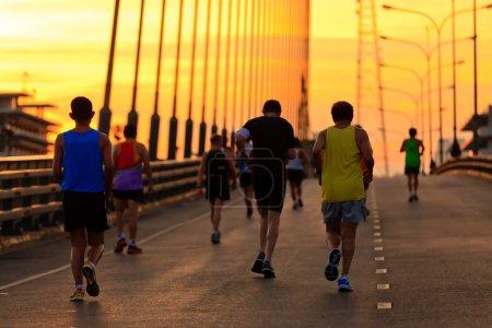 Runners run on bridge in the morning