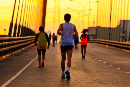 Runners run on bridge in the morning