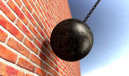 Photo for A regular metal wrecking ball attached to a chain hitting and breaking a face brick - Royalty Free Image