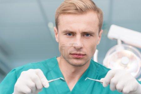Photo pour Portrait d'un dentiste sérieux tenant du matériel dentaire - image libre de droit