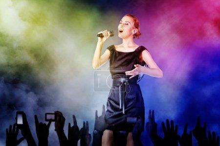 Photo pour Portrait d'une femme chantant pour ses fans lors d'un concert - image libre de droit