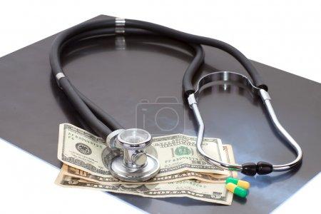 Photo pour Composition de l'image stéthoscope, radiographie, dollars et pilules - image libre de droit