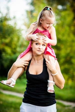 Mother and daughter on a piggyback in park