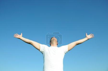Photo pour Jeune homme en t-shirt blanc bras ouverts, ciel bleu. Au-dessus de l'espace pour le texte ou les graphiques . - image libre de droit