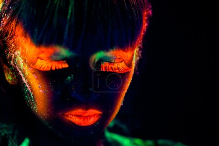 Photo pour Woman's face with fluorescent bodyart. Black background. Studio shot - image libre de droit