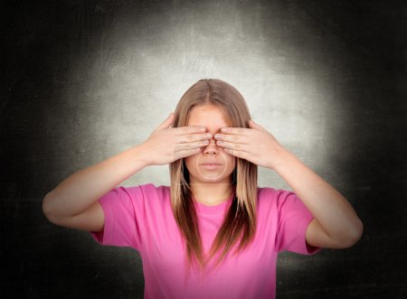 Portrait Of Young Woman Covering Her Eyes Over Bac...