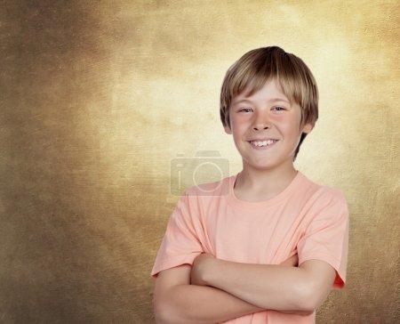 Photo pour Adolescent souriant avec un geste heureux sur un fond irrégulier ocre - image libre de droit