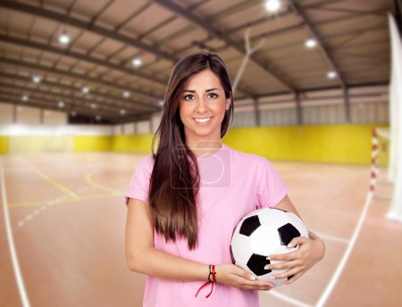Photo pour Fille tractive avec un ballon de football dans le centre sportif - image libre de droit
