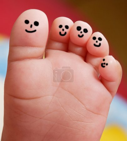 Photo for Nice foot of a baby with smiley faces painted toes - Royalty Free Image