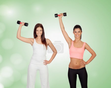Two brunette girls tightening their muscles