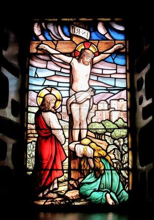 Foto de Ventana de color con la imagen del Jesús crucificado y María llorando - Imagen libre de derechos