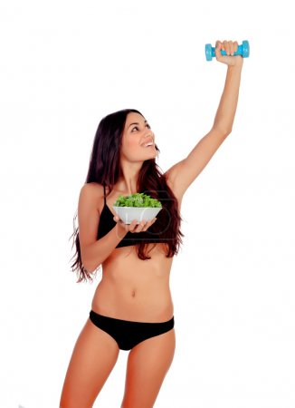 Girl in white underwear with a salad and exercising with dumbbel
