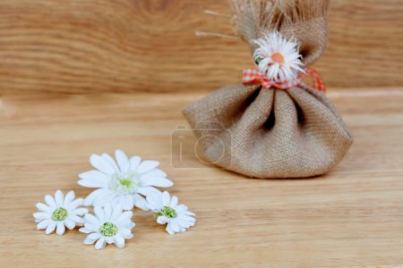 Brown bag closed with a ribbon and flowers