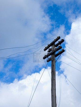 Telegraph pole over blue sky background