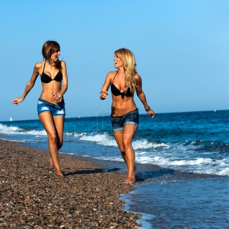 Attractive girl friends running along seaside.