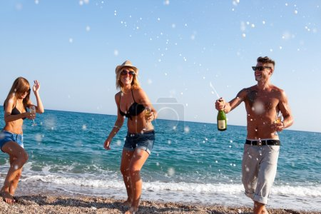 Photo for Group of friends dancing under champagne bubbles on beach. - Royalty Free Image