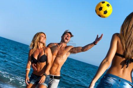 Friends having fun on beach with ball.