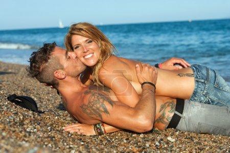 Photo pour Jeune couple sexy attrayant embrasser sur la plage de galets . - image libre de droit