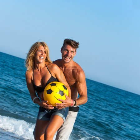 Young couple having fun with ball on beach.