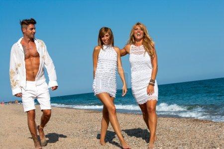 Young friends walking along sunny beach.