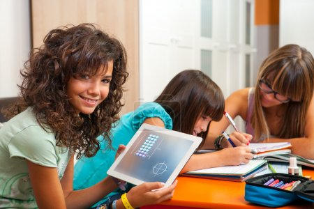 Young girl showing homework on tablet indoors.