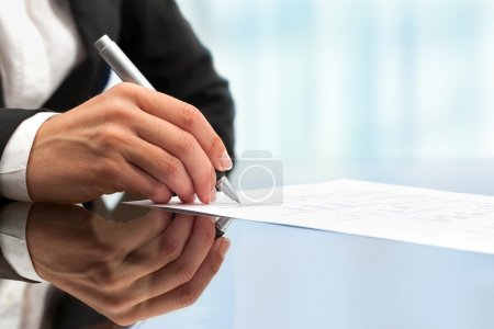 Photo for Extreme clos up of female business hand signing document. - Royalty Free Image