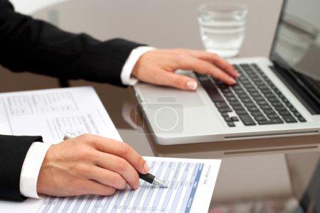 Photo pour Gros plan des mains féminines examinant les documents comptables sur la table . - image libre de droit