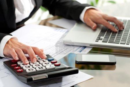 Photo pour Gros plan des mains de femmes travaillant sur la calculatrice et l'ordinateur portable. - image libre de droit