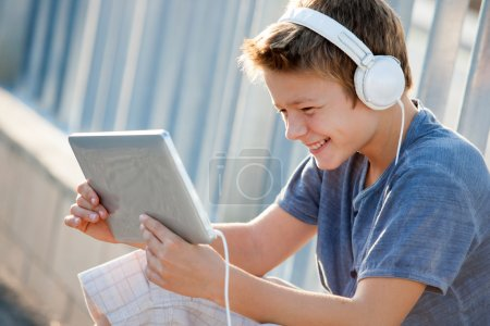 Cute teen boy with headphones and tablet.