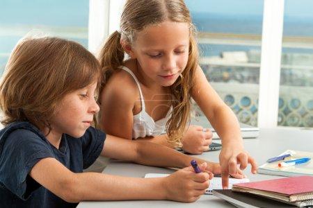 Girl helping boy with homework.