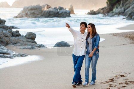 Young couple wandering along seashore.